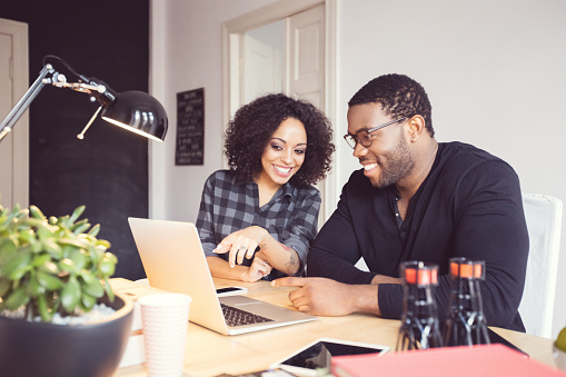 Two Designers In The Office Using Laptop Together Stock Photo - Download Image Now