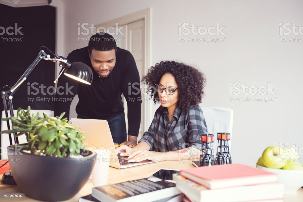 Two designers in the office, using laptop together Afro american young man and woman in the office, using laptop together. Adult Stock Photo
