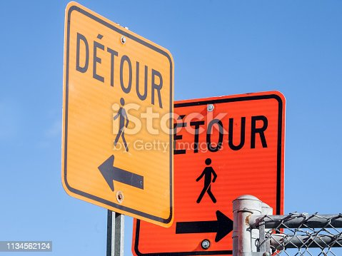 Picture of two construction signs, in orange color, taken in Montreal, Quebec, Canada, indicating a detour compulsory for pedestrians