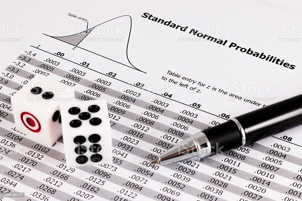 Two dice and pen on standard normal probabilities table. stock photo