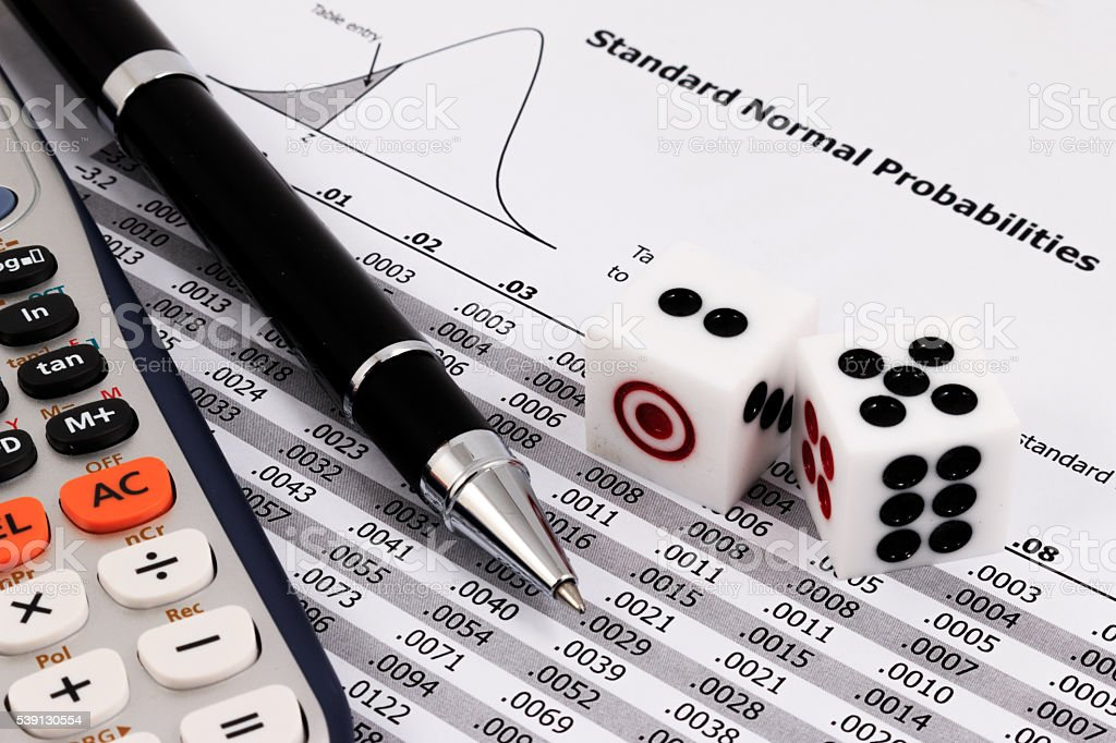 Two dice, calculator and pen on standard normal probabilities table. stock photo