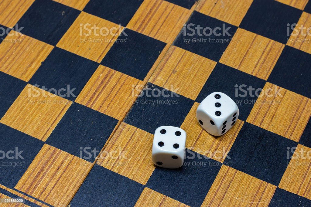 Two dice on chess board stock photo