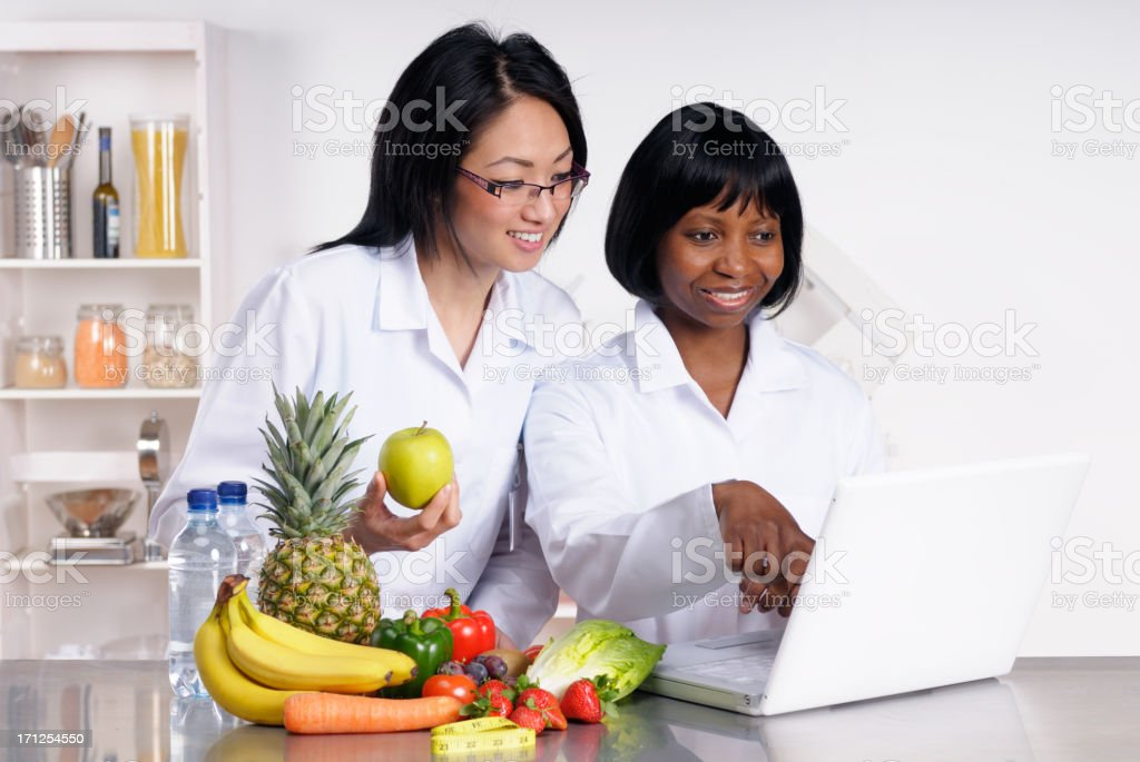 Two dietitians holding food and working online stock photo