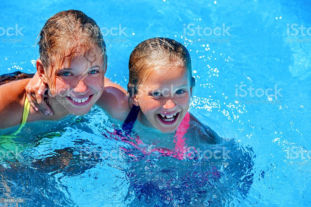 Two different ages children swim in swimming pool. - Photo