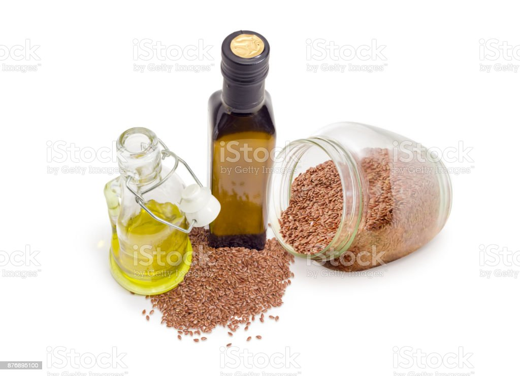 Two different bottles of linseed oil and linseeds stock photo