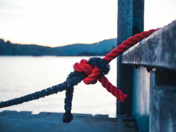 Zwei verschiedene farbige Seile gebunden zusammen an einem Liegeplatz – Foto