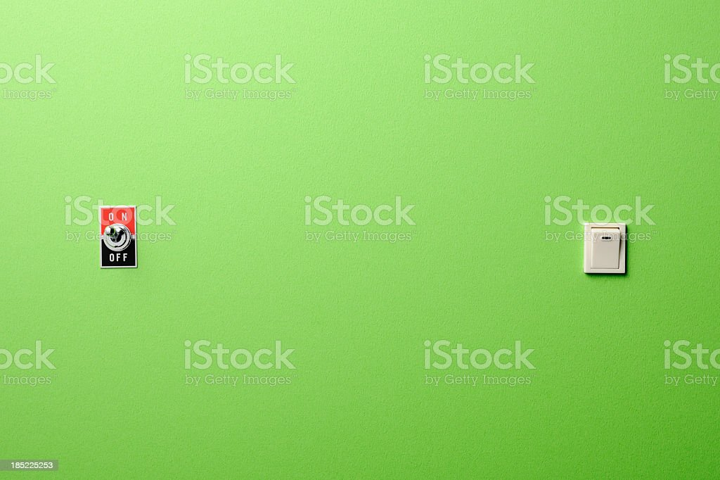 Two different ON/OFF switch on green wall. stock photo