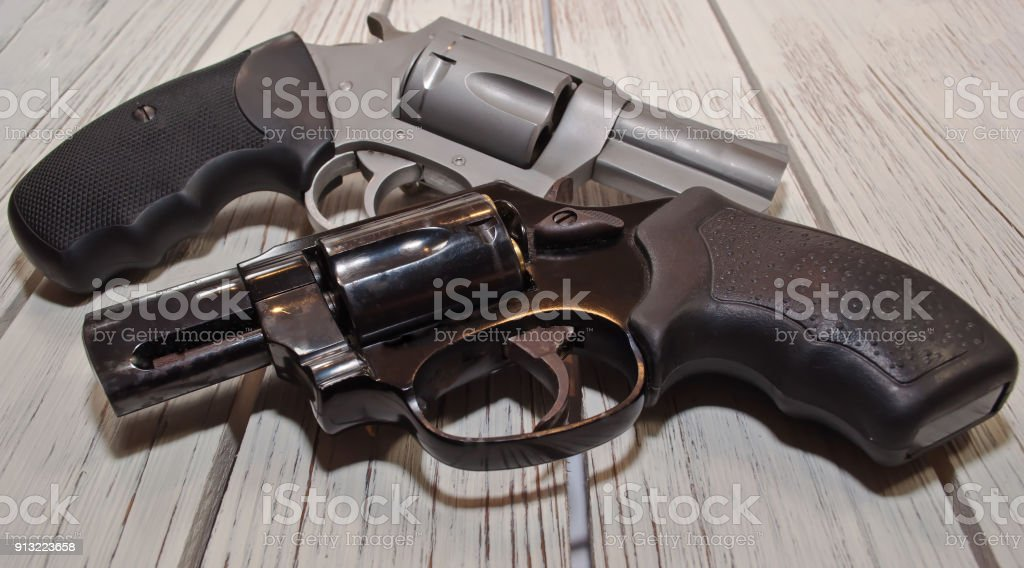 Two different revolver on a wooden table stock photo