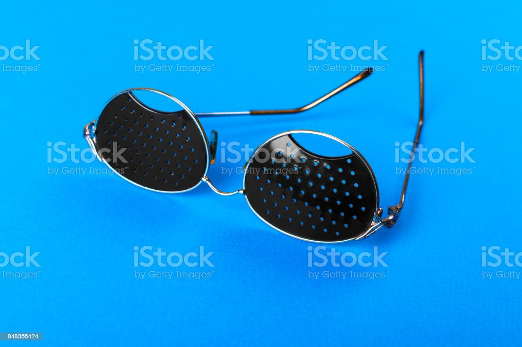 Two different type of glasses on blue background. Medical concept. Top view. Pinhole black eyeglasses help relaxing weary eyes Isolated on white background. Classic Fashion optical eyeglasses. stock photo