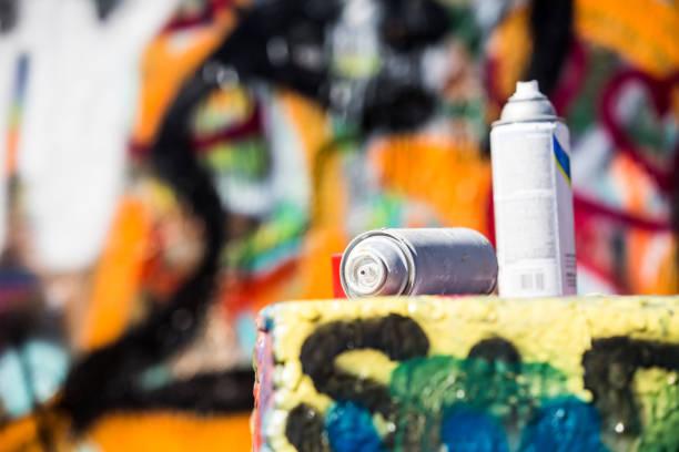 zwei ausrangierte spraydosen vor graffitiwand - schlechte laune sprüche stock-fotos und bilder