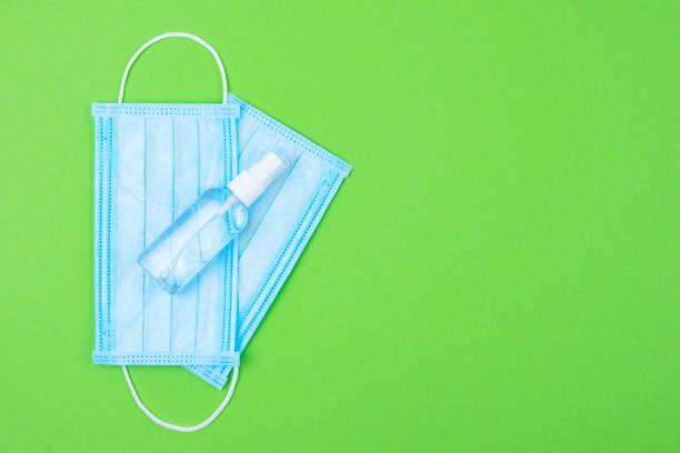 Zwei Einweg-medizinische chirurgische Schutzgesichtsmaske mit antibakteriellen antiseptischen Spray für Hände Desinfektionsmittel auf grünem Hintergrund. Schutz vor Virus, Grippe oder Coronavirus Covid-19, 2019-nCoV. Ort für Text. – Foto