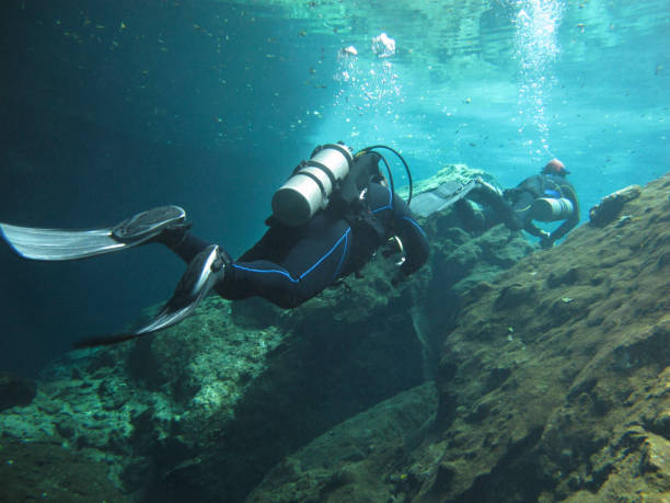 Two divers exploring the underwaters cenotes in Mexico. stock photo