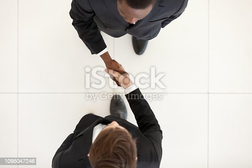 istock Two diverse businessmen shake hands standing in office, top view 1095047246