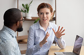 istock Two diverse businesspeople chatting sitting behind laptop in office 1156269842