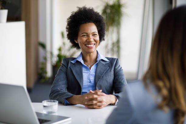 Two diverse businesswomen talking working together in office stock photo