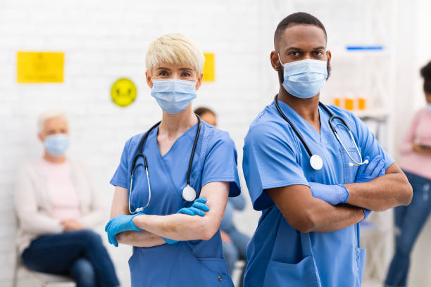 Two Diverse Doctors In Medical Masks Posing Standing In Hospital stock photo