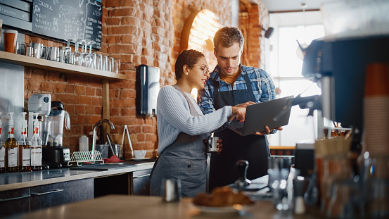 Two Diverse Entrepreneurs Have a Team Meeting in Their Stylish Coffee Shop. Barista and Cafe Owner Discuss Work Schedule and Menu on Laptop Computer. Multiethnic Female and Male Restaurant Employees.