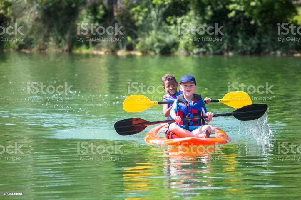 Two diverse little boys kayaking down a beautiful river royalty-free stock photo
