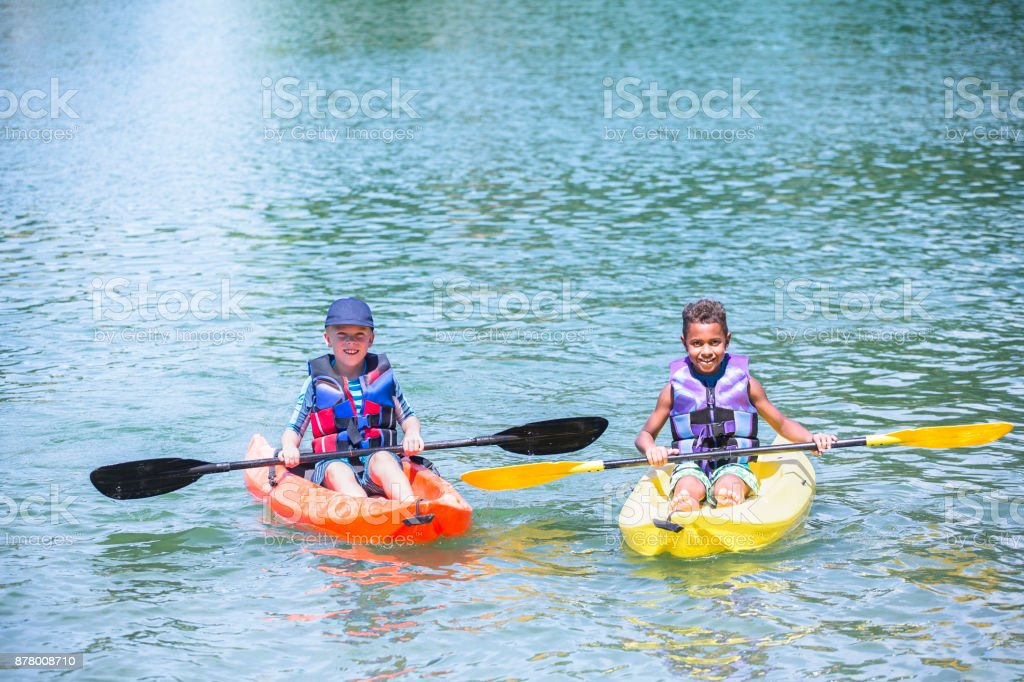 Two diverse little boys kayaking on a beautiful lake stock photo
