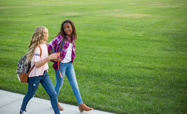 Two diverse school kids walking home together after school stock photo