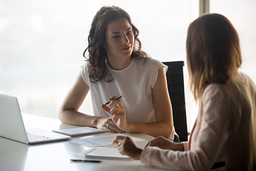 istock Two diverse serious businesswomen talking working together in office 1128967599