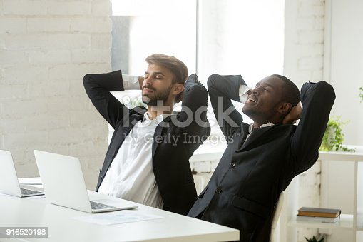 istock Two diverse young businessmen relaxing at work breathing fresh air 916520198