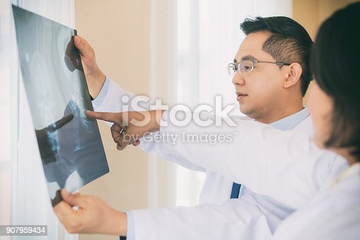 istock Two Doctor talking and examining x-ray film about result and background blur operating room with X-ray medical scan at hospital. 907959434