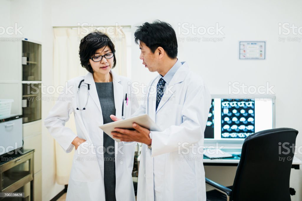 Mature male and female japanese doctors discussing results of a...