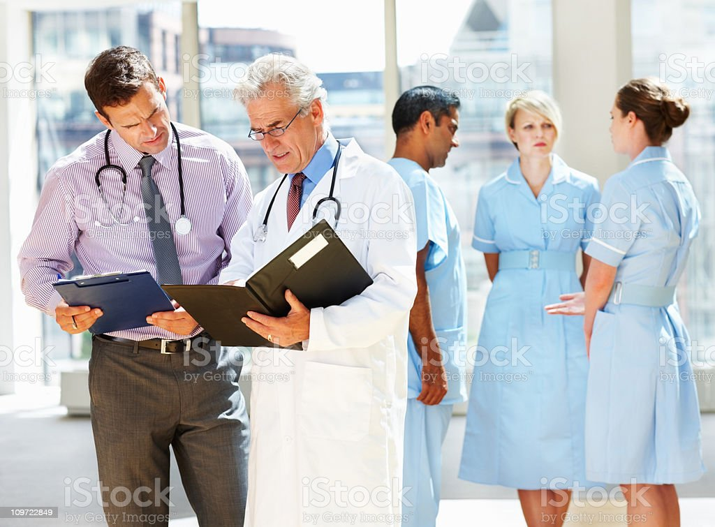 Two doctors discussing while their team in background royalty-free stock photo