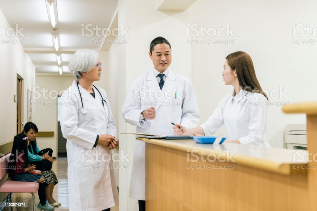 Japanese doctors talking to female colleague in hospital waiting...