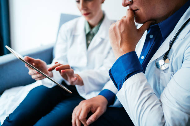 Two doctors having conversation over a case in doctor's office. Shot of a two confident doctors at a meeting. Doctor and nurse sitting on the sofa and discussing over a medical report in doctor's office.  Healthcare staff having discussion in the hospital. Two doctors having discussion about patient diagnosis, using digital tablet. medical technology stock pictures, royalty-free photos & images
