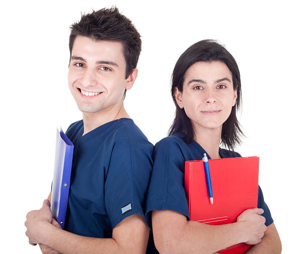 Two doctors holding folders and wearing scrubs stock photo