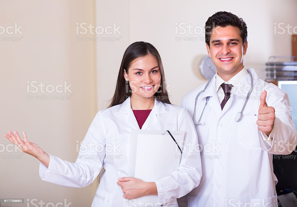 Portrait of smiling doctor and his young assistant in private clinic