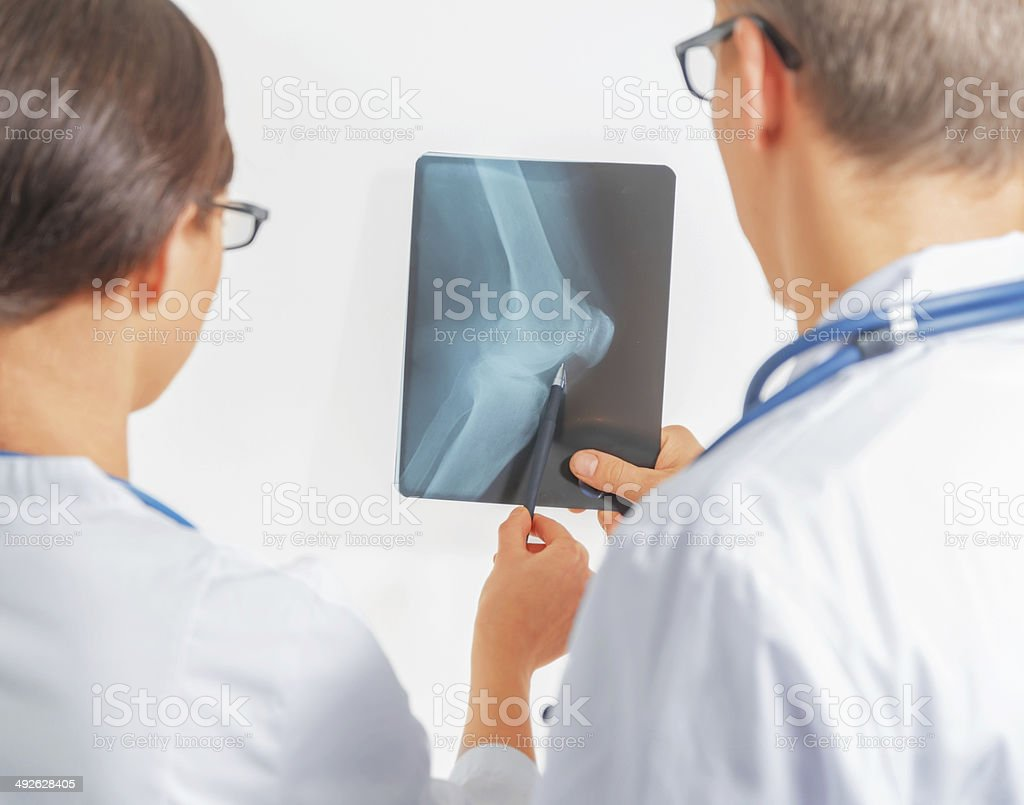 Two doctors look at x-ray image stock photo