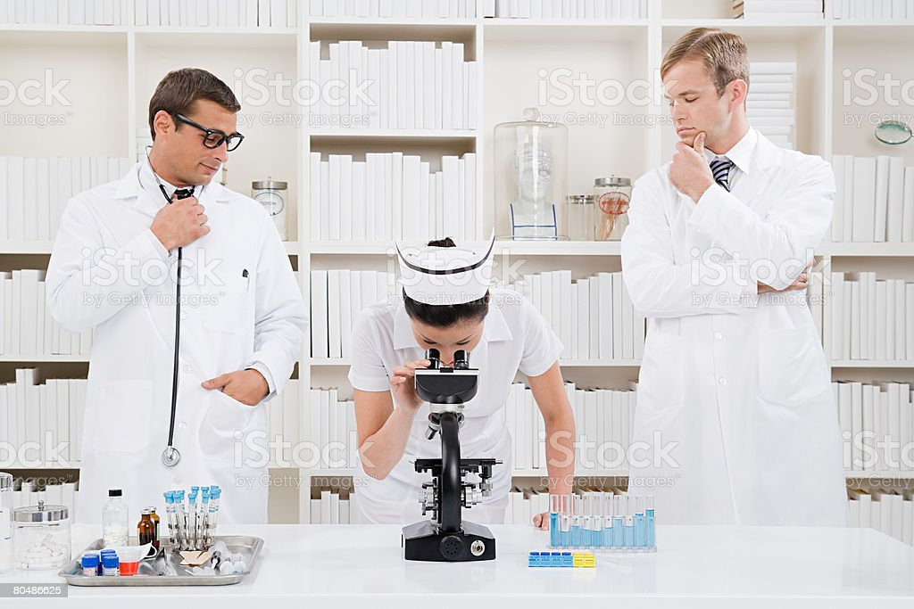 Two doctors looking at a nurse 免版稅 stock photo