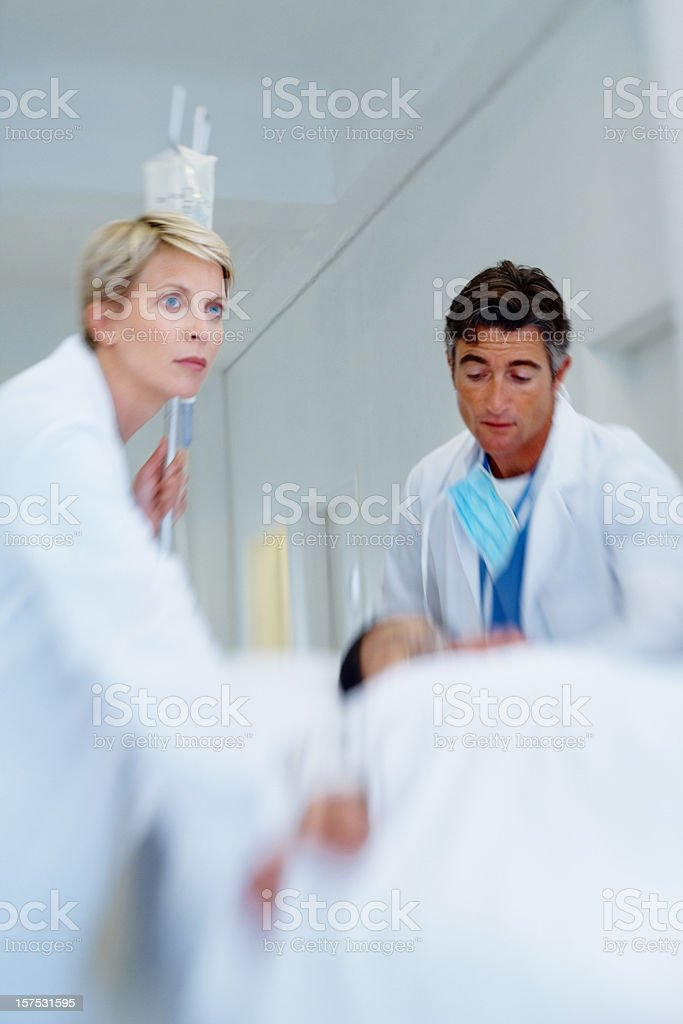 Two doctors rushing through hall with patient royalty-free stock photo