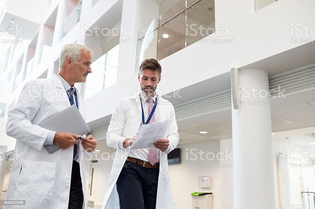 Two Doctors Talking As They Walk Through Modern Hospital stock photo