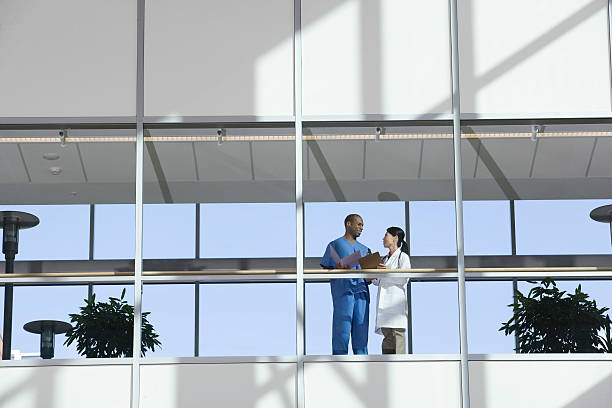 two doctors talking in corridor - hospital building stock photos and pictures