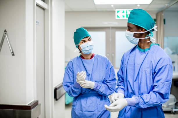 Two doctors talking together on the way to a hospital operating room stock photo