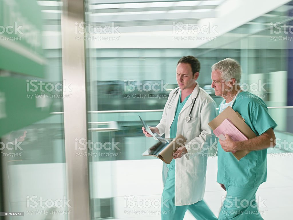 Two doctors wearing scrubs walking in hurry in hospital royalty-free stock photo