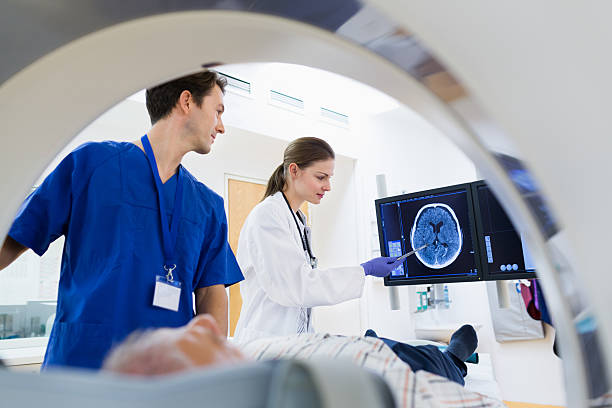 Two Doctors with Patient at CAT Scan stock photo
