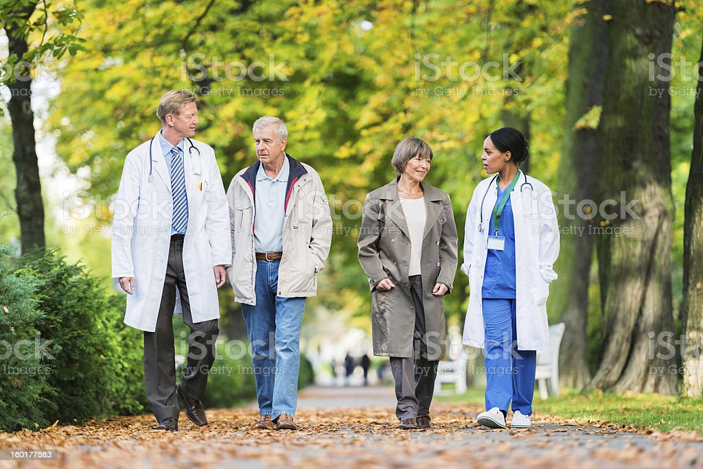 Two Doctors With Senior Couple Having a Walk royalty-free stock photo