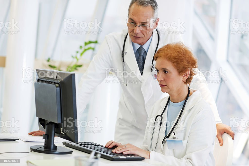 Two doctors working on a computer. royalty-free stock photo