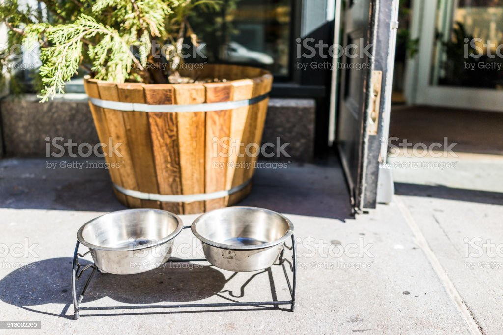 Two dog water bowl plates outside restaurant store shop in NYC New York City urban Manhattan entrance door on sidewalk with nobody closeup stock photo