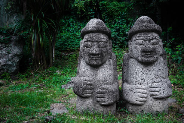 Two Dol Hareubang statues in dark green forest, Seogwipo, Jeju Island, South Korea stock photo