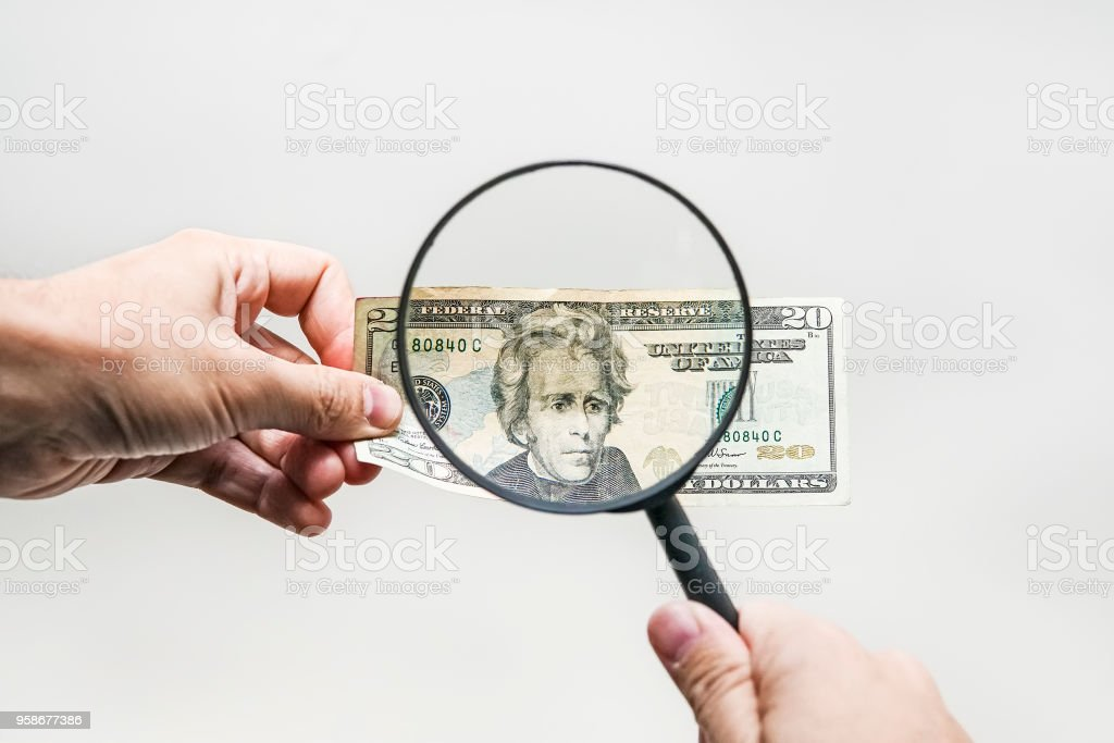two dollar bill and magnifying glass isolated on white stock photo