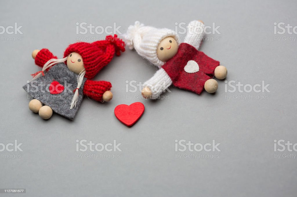 Two dolls in love on Valentines day knitted wear with heart postcard
