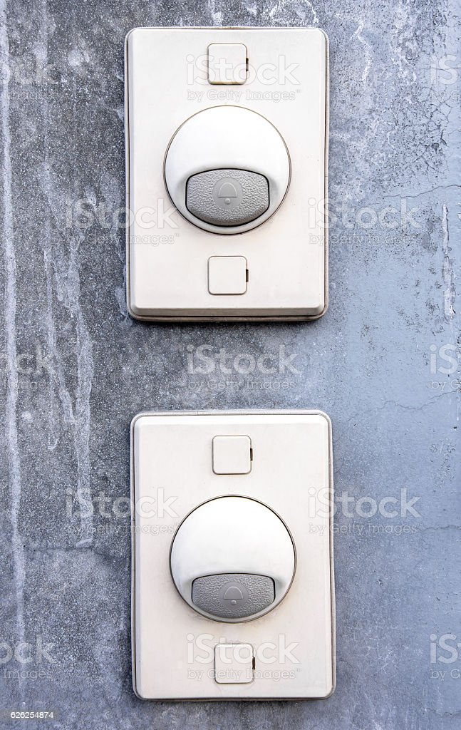 Two doorbell ring button on concrete wall stock photo