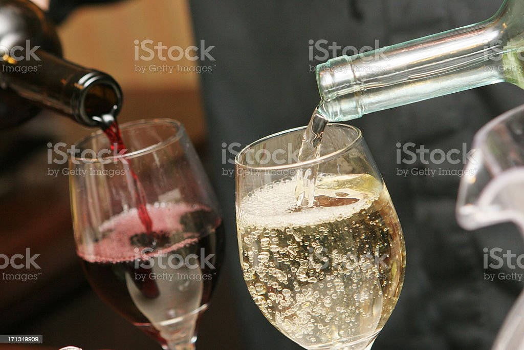 Two drinking glasses being filled with red and white wine royalty-free stock photo