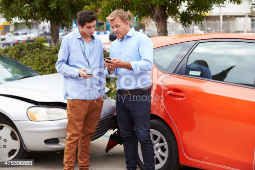 475395935istockphoto Two Drivers Exchange Insurance Details After Accident 475396889